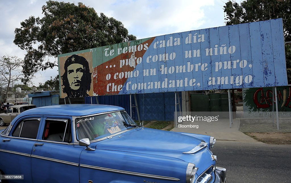 A car drives past a billboard saluting revolutionary Che Guevara in Havana, Cuba, on Wednesday, March 6, 2013. Cuba's government praised Venezuelan President Hugo Chavez following his death yesterday for uniting the people of Latin America and pledged loyalty to the continuation of his Bolivarian Revolution, according to the statement in the state-run Granma website. Photographer: Noah Friedman-Rudovsky/Bloomberg via Getty Images