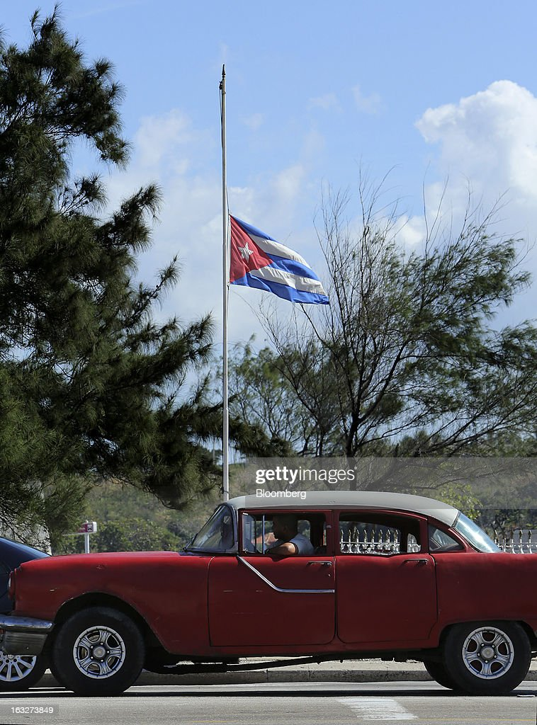 A car drives past a Cuban flag flying at half mast in Havana, Cuba, on Wednesday, March 6, 2013. Cuba's government praised Venezuelan President Hugo Chavez following his death yesterday for uniting the people of Latin America and pledged loyalty to the continuation of his Bolivarian Revolution, according to the statement in the state-run Granma website. Photographer: Noah Friedman-Rudovsky/Bloomberg via Getty Images