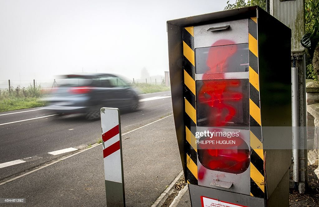 A car drives past a defaced speed radar on September 1, 2014 near the northern French town of Vieux-Berquin.