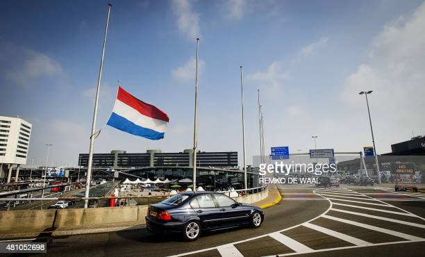 A car drives past a Dutch flag flying at halfmast at the airport in Schiphol the Netherlands on July 17 as relatives remembered their dead in...