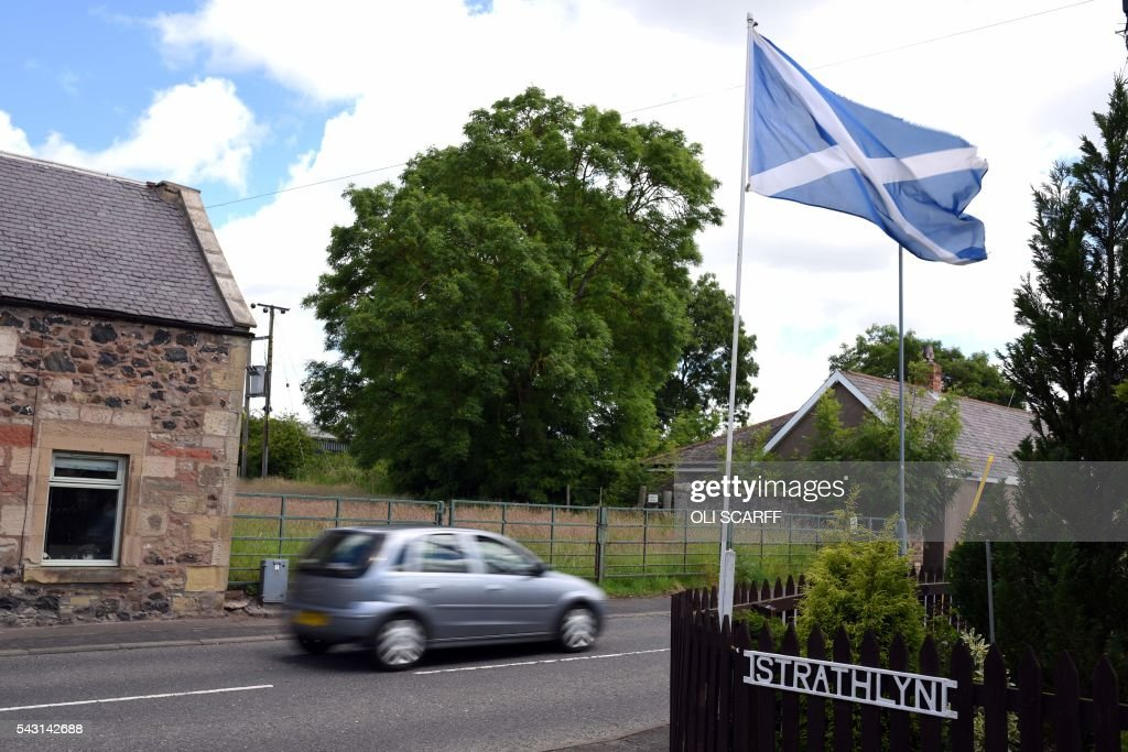A car drives past a house with a Scottish Saltire flag flying outside in the border village of Birgham, Scotland on June 26, 2016. Scotland's First Minister Nicola Sturgeon campaigned strongly for Britain to remain in the EU, but the vote to leave has given the Scottish National Party leader a fresh shot at securing independence. Sturgeon predicted more than a year ago that a British vote to leave the alliance would give pro-European Scots cause to hold a second referendum on breaking with the UK. SCARFF