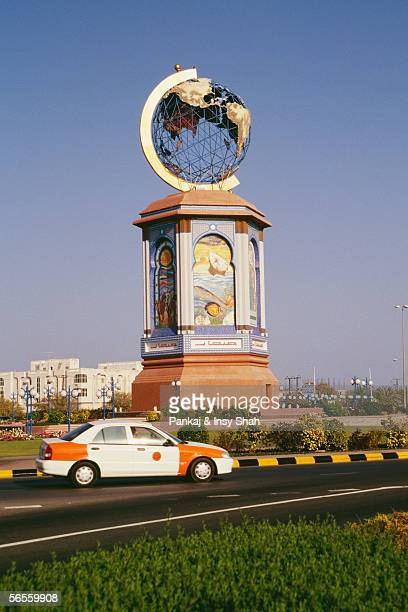 A car drives past a huge painted structure with earth on the top near Sohar