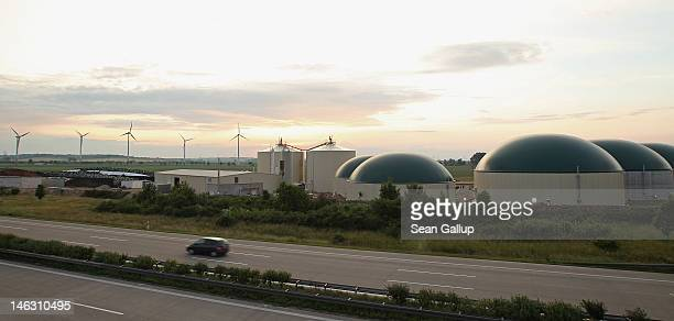 A car drives past a new biogas plant as wind turbines spin behind in Lower Saxony on June 12 2012 near Ebendorf Germany The plant processes natural...