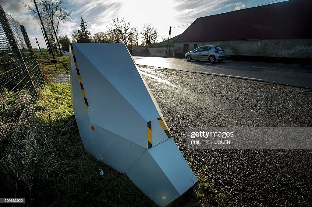 A car drives past a speed camera on the D939 in Aubigny-en-Artois on February 10, 2016, in the first area in France to be outfitted with 'luring signs'. Eleven signs reading 'For your safety, frequent use of speed cameras' will be installed on a portion of the by-road in the Pas-de-Calais department, but a speed camera will be hidden behind only one of the signs, which will be moved regularly. / AFP / PHILIPPE HUGUEN
