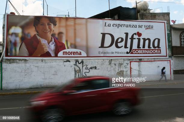 A car drives past a wall painted with campaign publicity for Delfina Gomez the National Regeneration Movement's candidate for governor of the state...