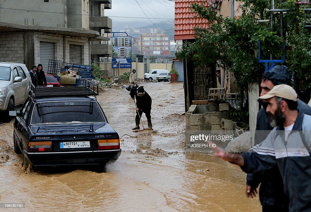 A car drives past a woman flushing water and mud from the entrance of her flooded house in Beirut's southern impoverished suburb of Hayy al-Sellum on January 9, 2013 as heavy rains and high speed winds hit Lebanon. A met office official at Beirut airport said the storm would continue and that lower temperatures would result in snowfall in the mountains as low as 300 metres. AFP PHOTO /JOSEPH EID