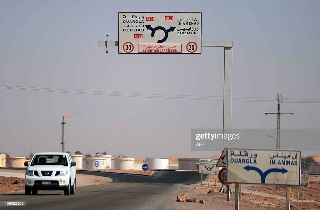 A car drives past an oil installation on the outskirts of In Amenas, deep in the Sahara near the Libyan border, on January 18, 2013. Islamist hostage-takers at a nearby gas field in the area, more than 1,300 kms southeast of the capital Algiers, demanded a prisoner swap and an end to the French military campaign in Mali, a report said, while 30 foreigners were reported still missing in the worst international hostage drama for years. AFP PHOTO/FAROUK BATICHE