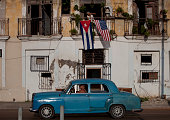A car drives past as American and Cuban flags fly on the balcony of a home in Havana Cuba on Monday July 20 2015 A diplomatic freeze that stretched...