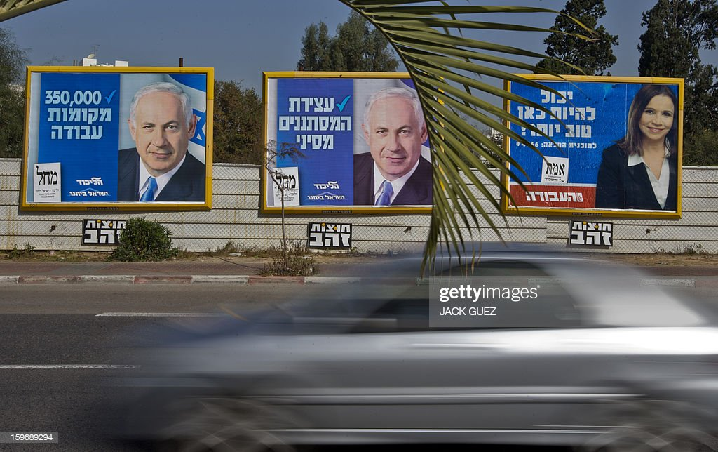 A car drives past election campaign posters for Israeli Prime Minister Benjamin Netanyahu (L) and Israeli Labor party leader Shelly Yachimovich (R) on January 18, 2013 in the Mediterranean coastal city of Tel Aviv ahead of the country's general elections on January 22.