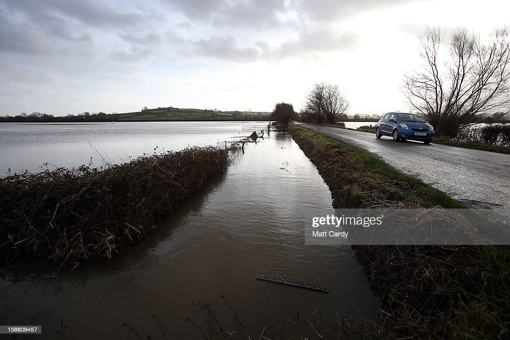A car drives past flood waters surrounding the village of Muchelney, which has been cut off by flooding on the Somerset Levels, on December 30, 2012 near Langport, England. The Met Office is warning of the risk of further flooding towards the end of the year, meaning 2012 is set to be the wettest on record.
