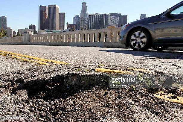 A car drives past potholes and broken asphalt on West 1st Street in Los Angeles California US on Friday Jan 21 2011 The US transportation network for...
