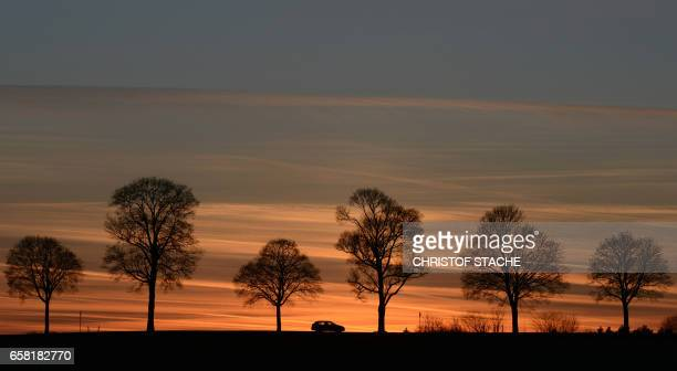 A car drives through a country as sun sets near the small Bavarian village of Haimhausen close to Munich southern Germany on March 26 2017...