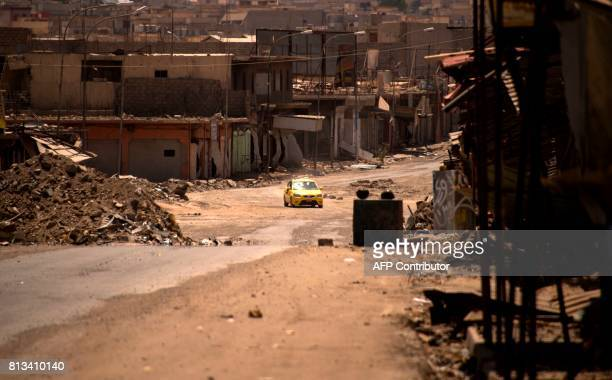 A car drives through a damaged street in west Mosul on July 12 2017 a few days after the government's announcement of the 'liberation' of the...