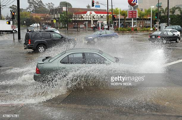 A car drives through a flooded intersection in Studio City California six miles north of Hollywood California February 28 2014 Heavy rains hit...