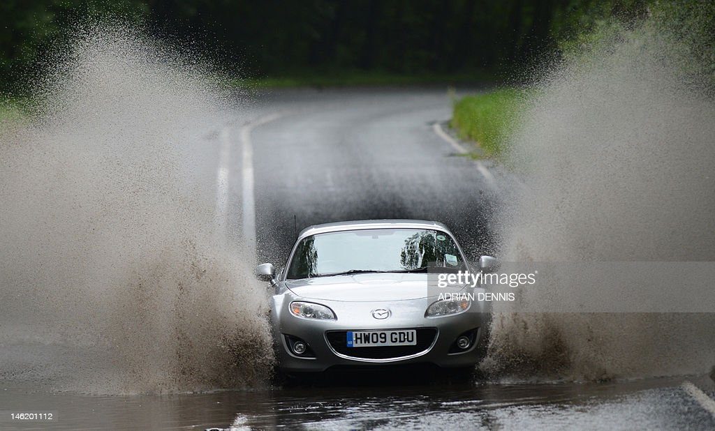A car drives through a large puddle on a road amid persistent rain in the village of Winchfield in Hampshire on June 12, 2012. The Met office continued to issue weather warnings for southern and central England and Wales on June 12 with more rain expected to incearse the risk of surface water flooding and localised river flooding, as well as causing difficult driving conditions.