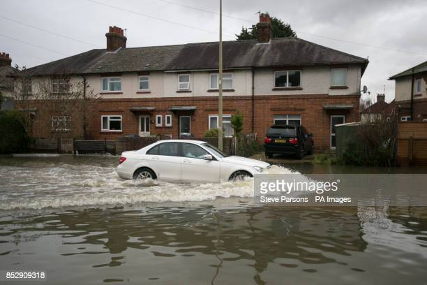 A car drives through Abingdon Road in Oxford which has flooded as heavy rain continues across the country