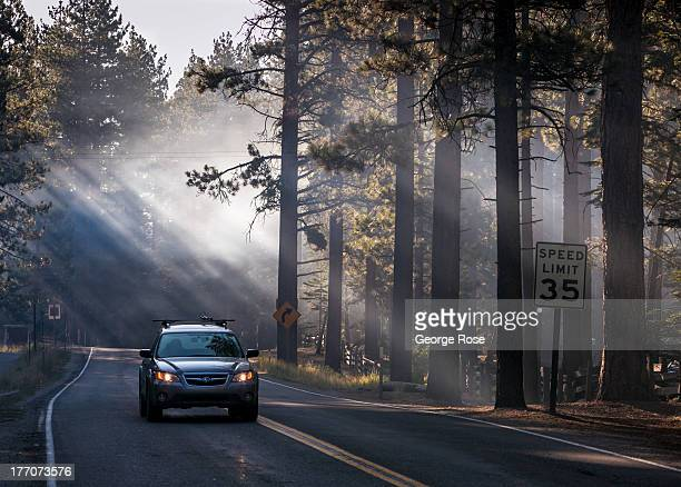 A car drives through campfire smoke along Highway 89 near Camp Richardson on August 4 in South Lake Tahoe California Lake Tahoe straddling the border...