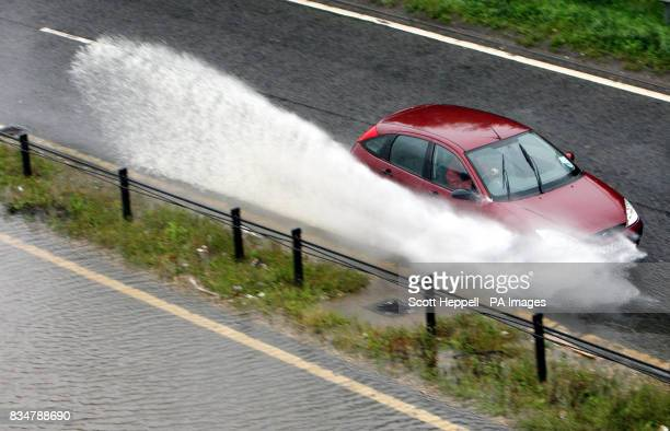 A car drives through flood water on the A167 in Newcastle where heavy rain has closed the southbound side carriageway