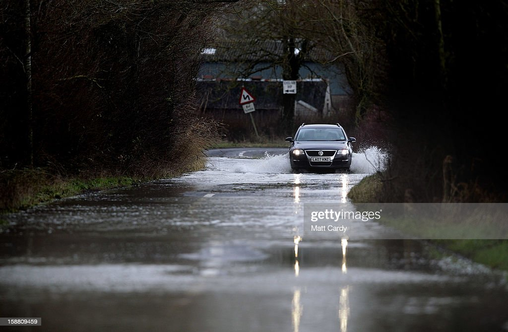 A car drives through flood waters surrounding the village of Muchelney, which has been cut off by flooding on the Somerset Levels, on December 30, 2012 near Langport, England. The Met Office is warning of the risk of further flooding towards the end of the year, meaning 2012 is set to be the wettest on record.