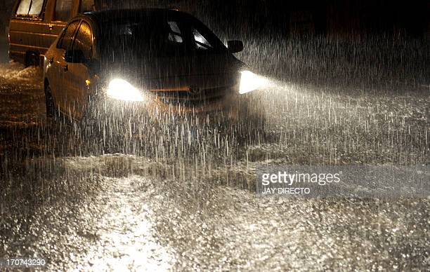 A car drives through heavy rain and floodwater in Manila on June 17 2013 The Philippine Atmospheric Geophysical and Astronomical Services...