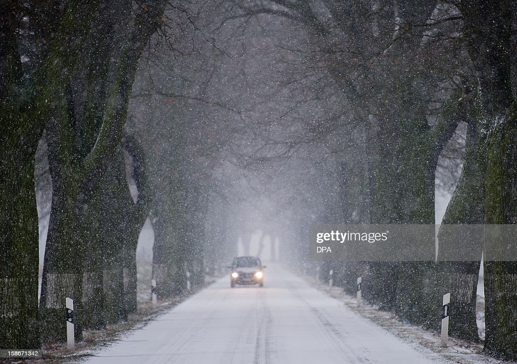 A car drives through snow on an alley near Petersdorf, northern Germany, on December 23, 2012.Temperatures around the freezing point led to icy conditions in northern and eastern parts of Germany. AFP PHOTO / PATRICK PLEUL GERMANY OUT