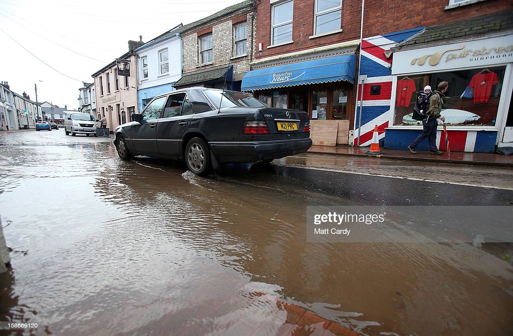 A car drives through the receding flood water in the centre of the Devonshire town of Braunton that was flooded yesterday on December 23, 2012 near Barnstaple, England. Flooding has brought further disruption to many parts of the UK including the South West of England that was particularly badly hit. The Met Office are warning of further bands of heavy rain tonight and the Environment Agency has issued 100s of flood warnings for England including one severe warning for Cornwall.