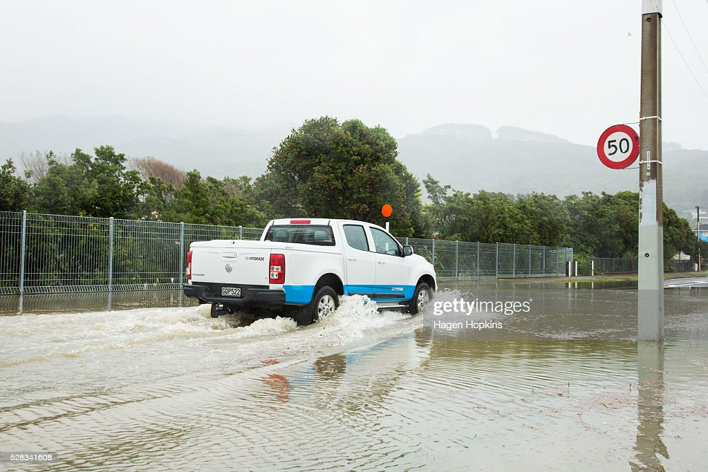 A car drives through water on Awarua Street after heavy rain caused flooding on May 5, 2016 in Porirua, New Zealand. Severe rain warnings have been issued for the bottom of the North Island, and and several schools and parts of the city have been closed due to surface floosing