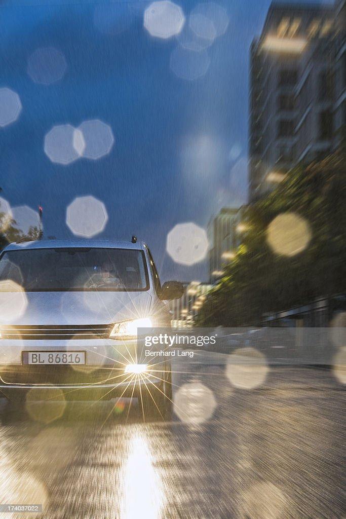 Car driving down urban road in rain