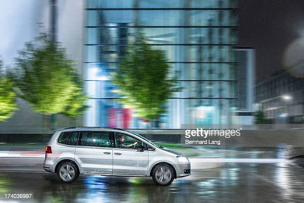 Car driving down urban street in rain
