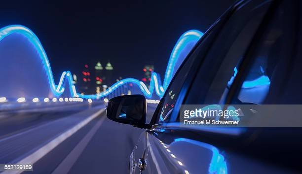 car driving nights over illuminated bridge
