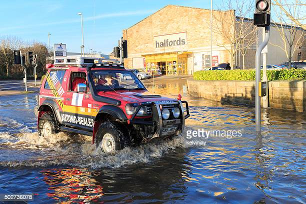 Car driving on a flooded street past shops in Leeds