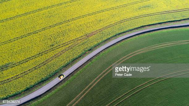 Car driving on country road between fields