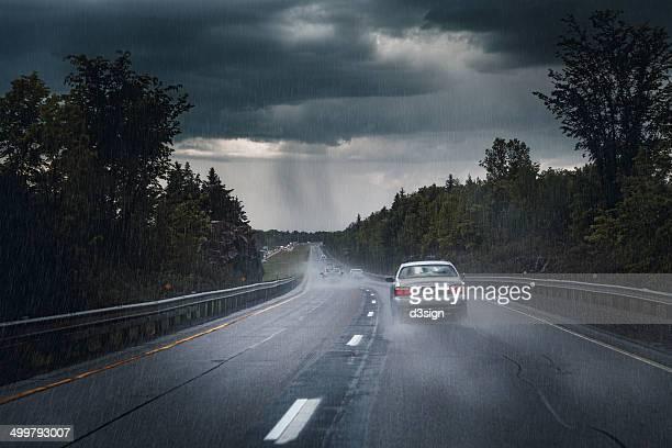 Car driving on highway under torrential rain