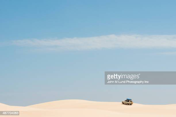 Car driving on sand dunes