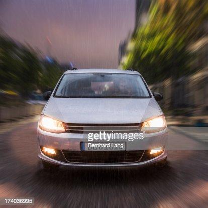 Car driving on urban street in the rain