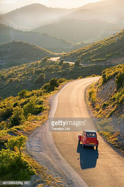 Car driving on winding road at sunset, elevated view