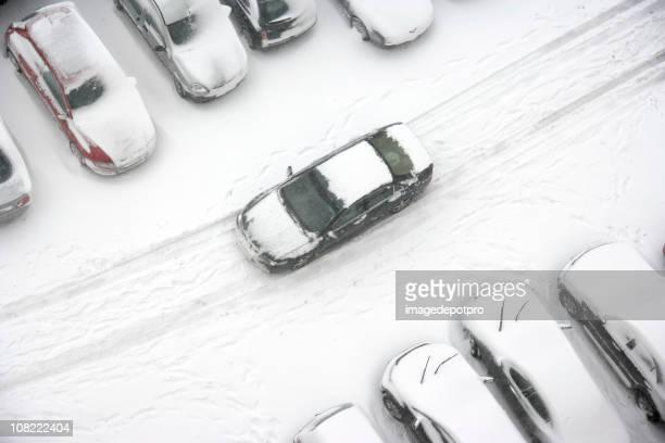 Car Driving Through Snowy Parking Lot