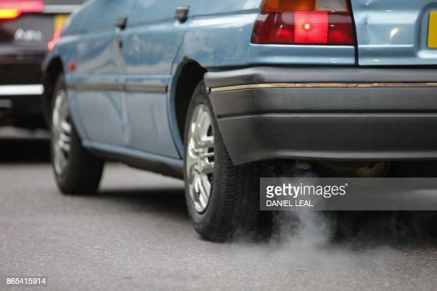 A car emits fumes from its exhaust as it waits in traffic in central London England on October 23 2017 Drivers of the most polluting vehicles will...