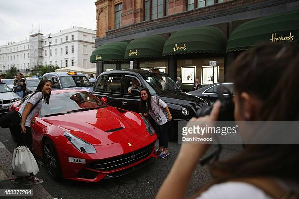 A car enthusiast takes a photograph of a Ferrari in Knightsbridge on August 8 2014 in London England Tourists and car enthusiasts have been flocking...