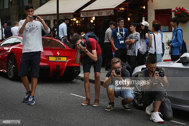 Car enthusiasts from Holland wait for supercars outside Harrods on August 8 2014 in London England Tourists and car enthusiasts have been flocking to...
