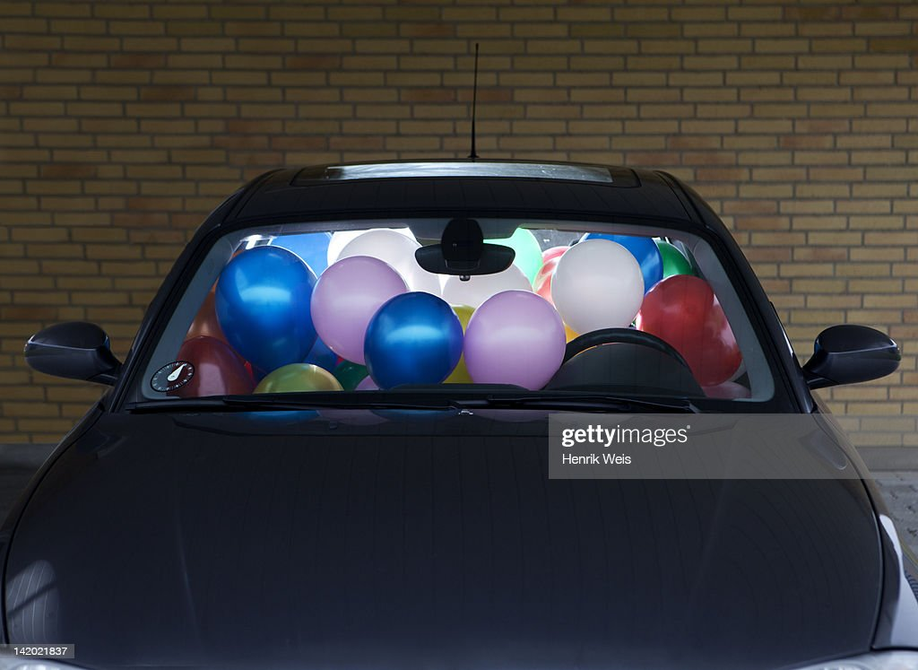 Car filled with colorful balloons