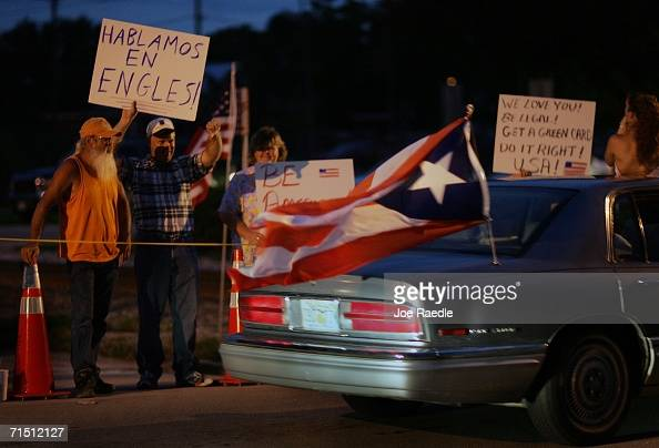 A car flying a Puerto Rican flag drives past people holding signs showing their support for a proposed municipal ordinance that would crack down on...