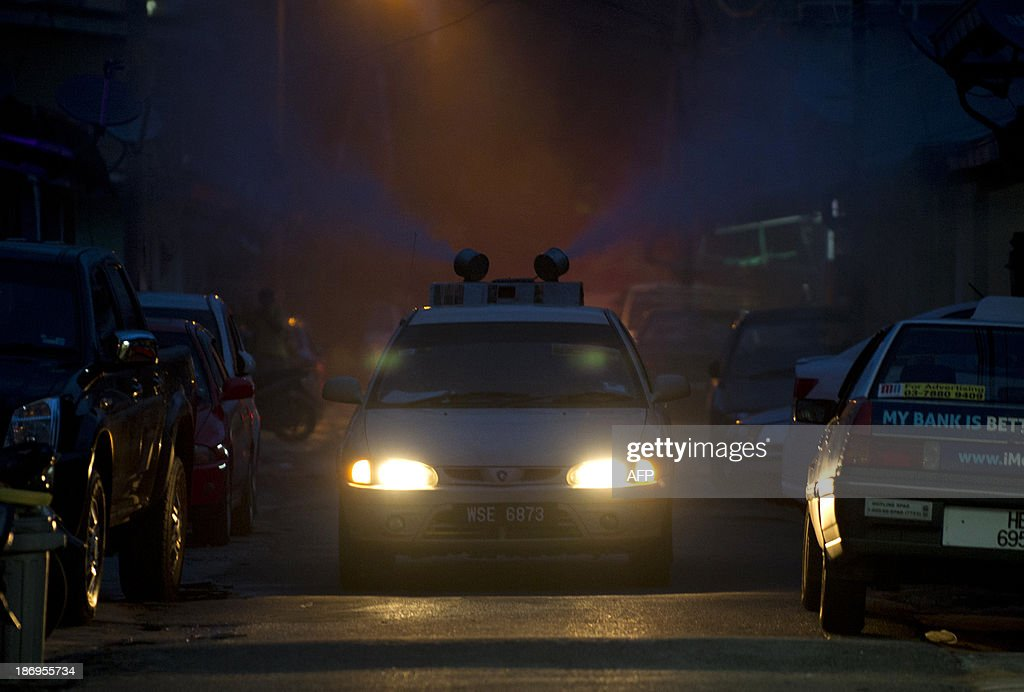 A car from the Malaysian ministry of health sprays dengue insecticide among residential houses in Gombak, on the outskirt of Kuala Lumpur on November 5, 2013. A Malaysian health official on November 4, warned citizens to take steps to eliminate mosquito breeding spots as dengue fever cases have spiked. AFP PHOTO / MOHD RASFAN