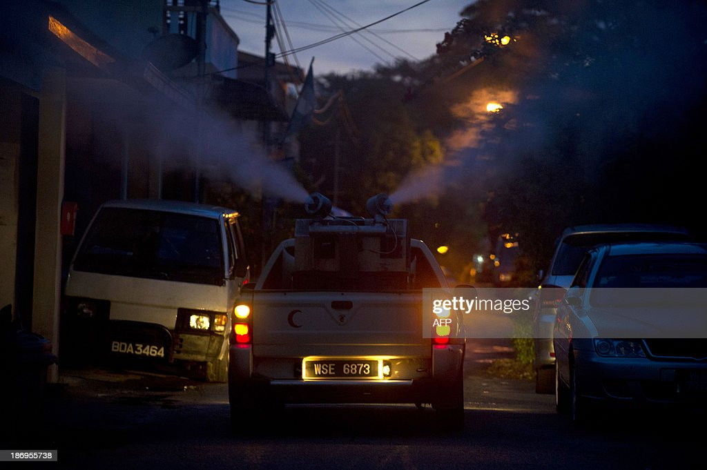 A car from the Malaysian ministry of health sprays dengue insecticide among residential houses in Gombak, on the outskirt of Kuala Lumpur on November 5, 2013. A Malaysian health official on November 4, warned citizens to take steps to eliminate mosquito breeding spots as dengue fever cases have spiked.