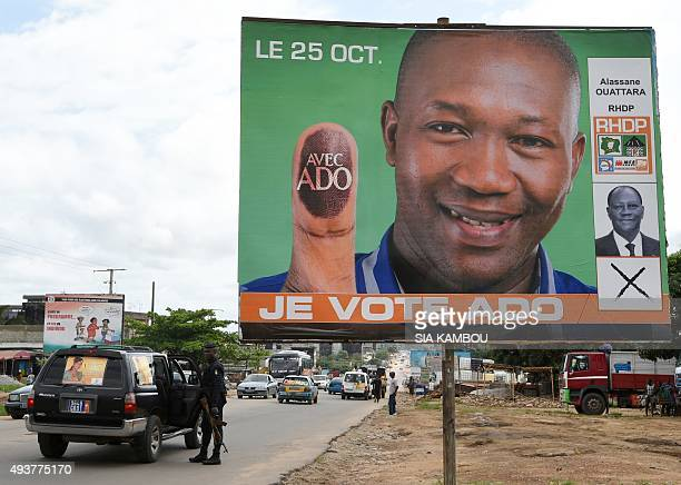 A car from the motorcade of Independent presidential candidate Jacqueline Claire Kouangoua stops by a campaign poster of outgoing President Alassane...