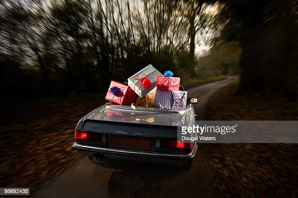Car full of presents on country lane.