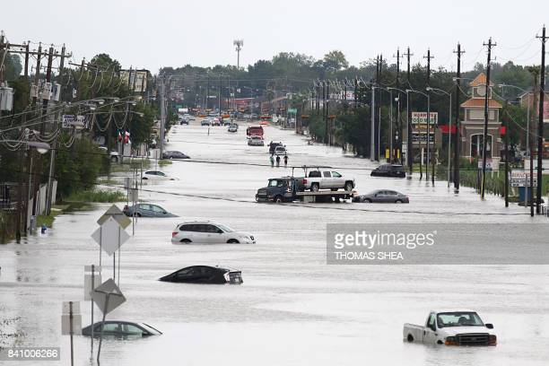 TOPSHOT A car gets towed while men walk in the flooded waters of Telephone Rd in Houston Texas on August 30 2017 Monster storm Harvey made landfall...