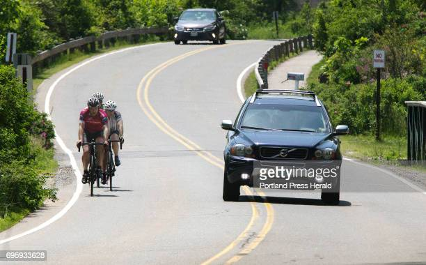 A car gives a wide berth to a peloton of cyclists on a narrow winding stretch near Pond Cove in Cape Elizabeth Maine law enforcement agencies will...