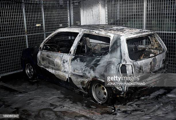 A car gutted by fire is parked in an indoor garage in the Stockholm suburb of Tureberg after youths rioted in several different suburbs around...