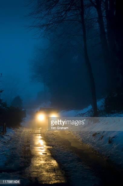 Car headlamps pierce the gloom on foggy day in The Cotswolds UK